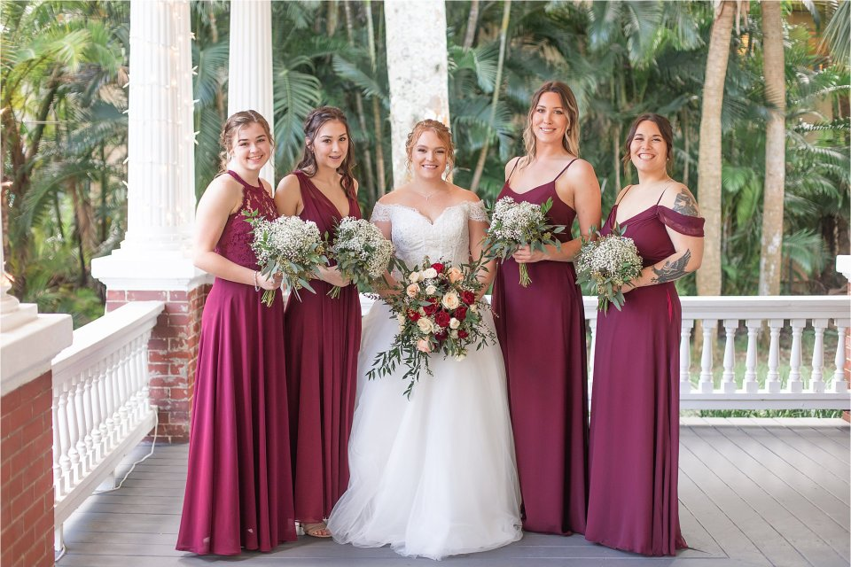 Bride and bridesmaids outside on porch at Heitman House in downtown Ft Myers, Florida wedding