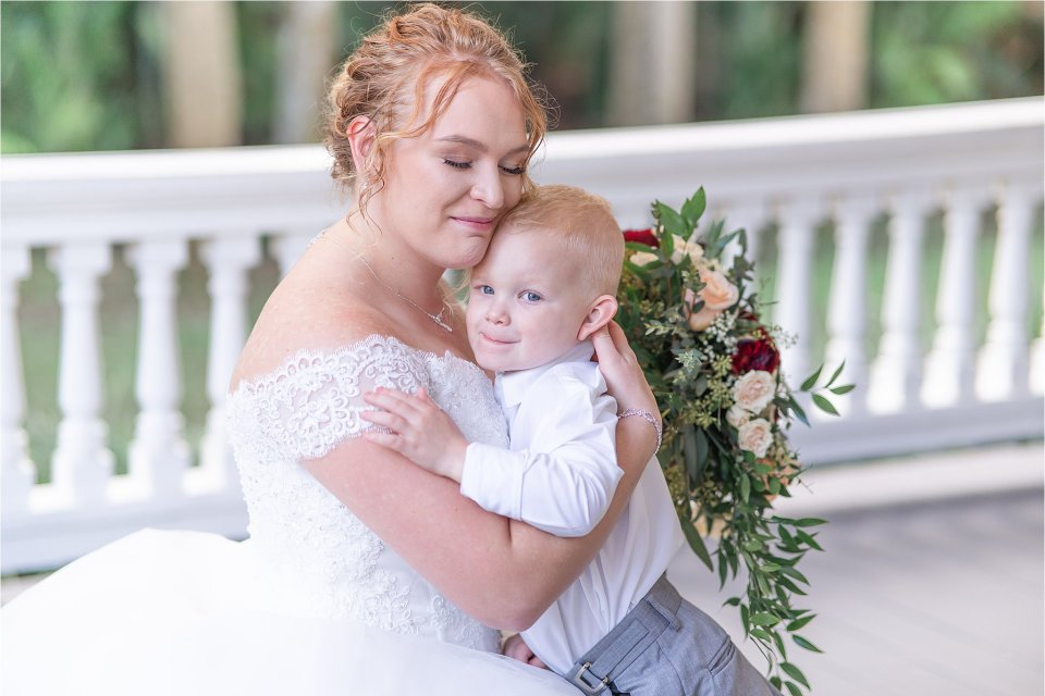 Bride and ring bearer son outside on porch at Heitman House in downtown Ft Myers, Florida wedding