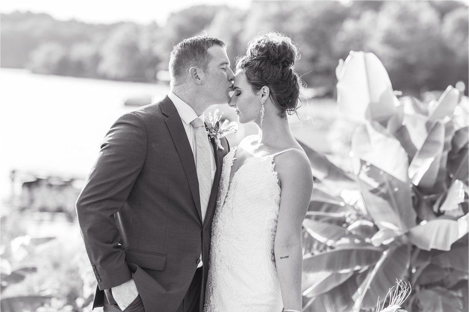 groom kissing bride's forehead in black and white