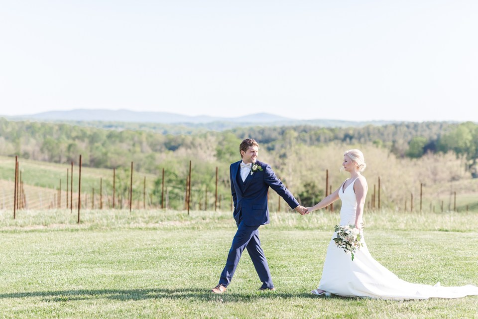 bride and groom walking on hillside at stone tower winery wedding