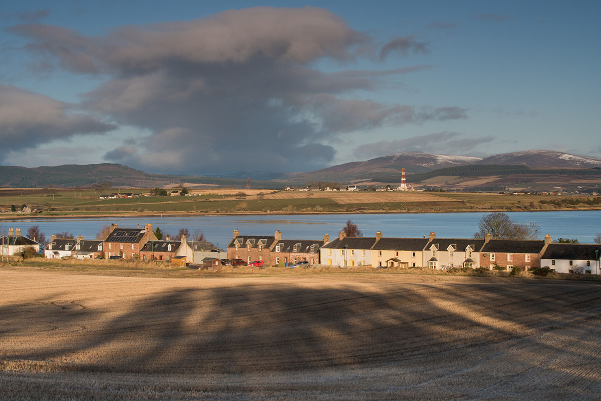 Black Isle photography - row of cottages between a barley field with shadows in the foreground and a bay on the other side