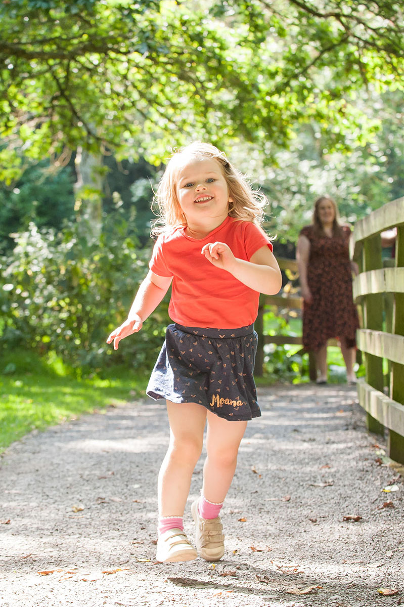 Young girl wearing an orange t-shirt and navy skirt smiling and running towards the camera on a gravel path beneath trees