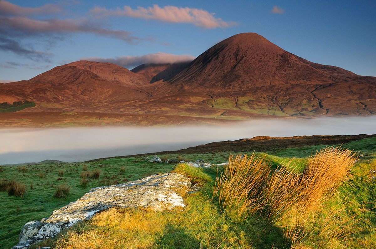 Rock and grass in the foreground, with mist in the valley beyond, overlooked by a mountain bathed in pink light