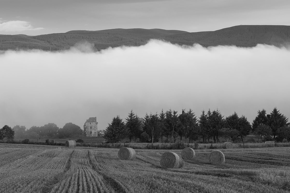 Black Isle photography - straw bales in a field with trees and a ruined castle beyond, with mist inversion and hills behind