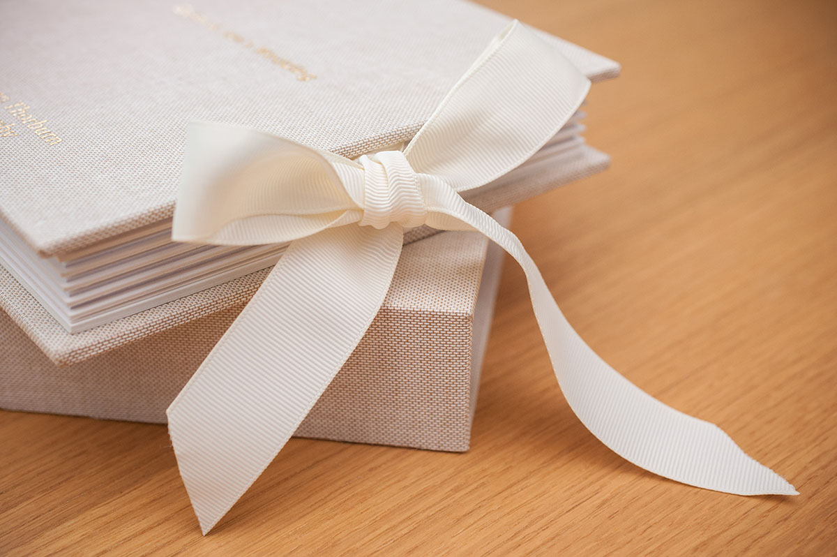 Wedding FAQS - cream ribbon tied in a bow on the side of a square wedding album sitting on a presentation box and oak table