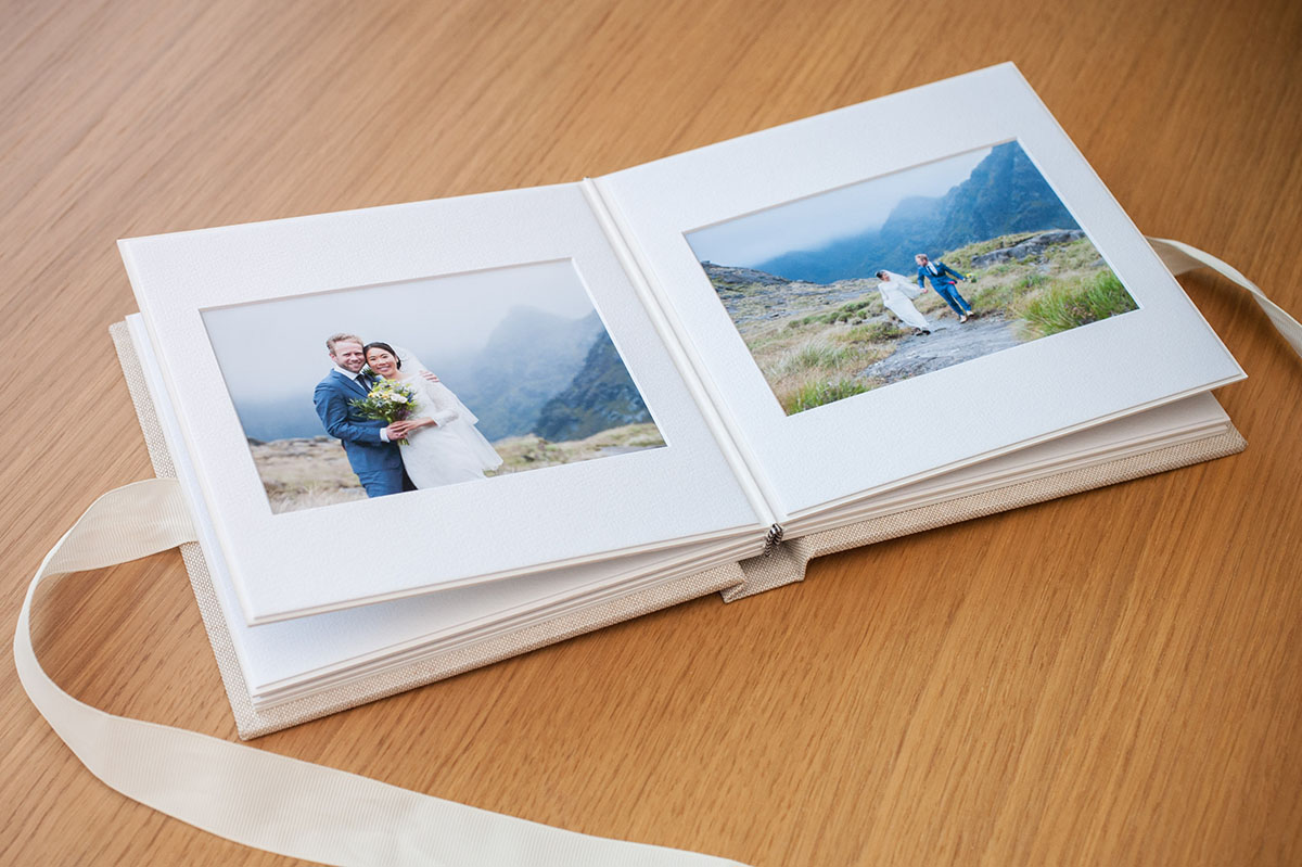Small square wedding album with a cream ribbon, open at a double page showing a bride and groom in front of mountains.
