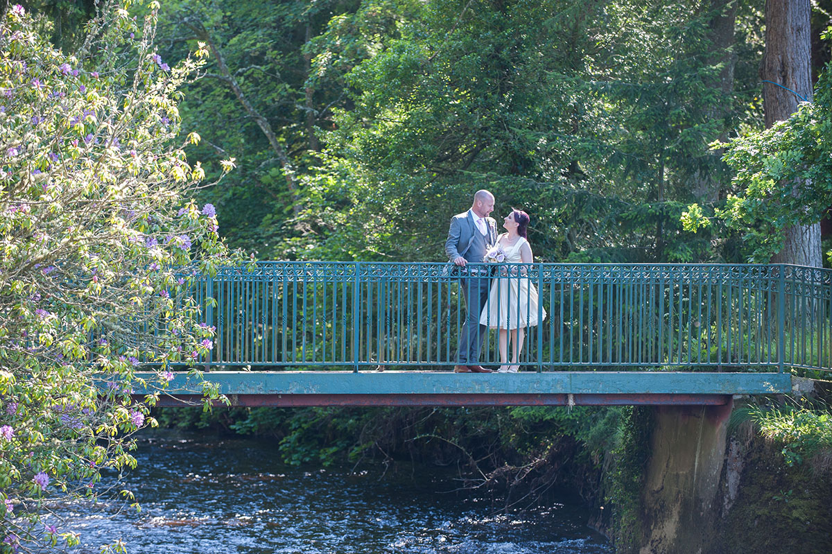 Wedding inspiration - bride and groom looking at each other, standing on a footbridge with the trees behind and a river below