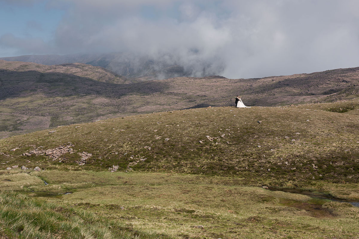Wedding inspiration - bride and groom in the distance, standing on a moorland hill with clouds on the mountains beyond