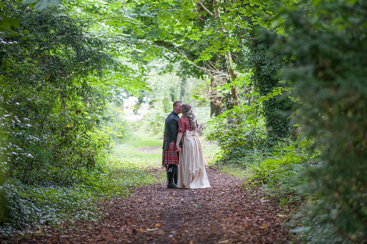 Wedding inspiration - bride in a red tartan top and cream skirt, kissing her groom in the woods with trees around them