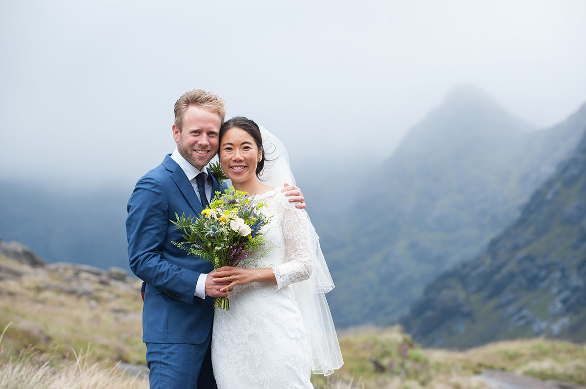 Wedding inspiration - groom in blue suit and bride in white dress with arms around each other in front of mountains and mist
