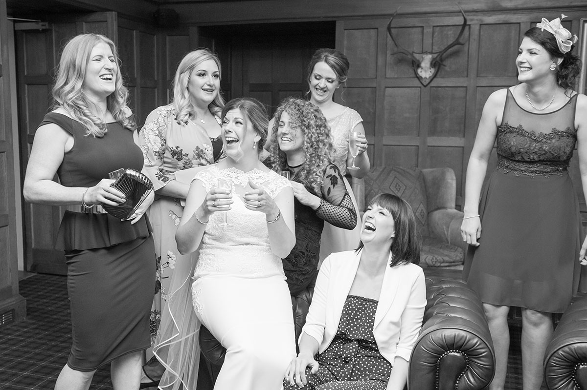 Wedding photo - monochrome image of a bride in a white dress, laughing, surrounded by female wedding guests
