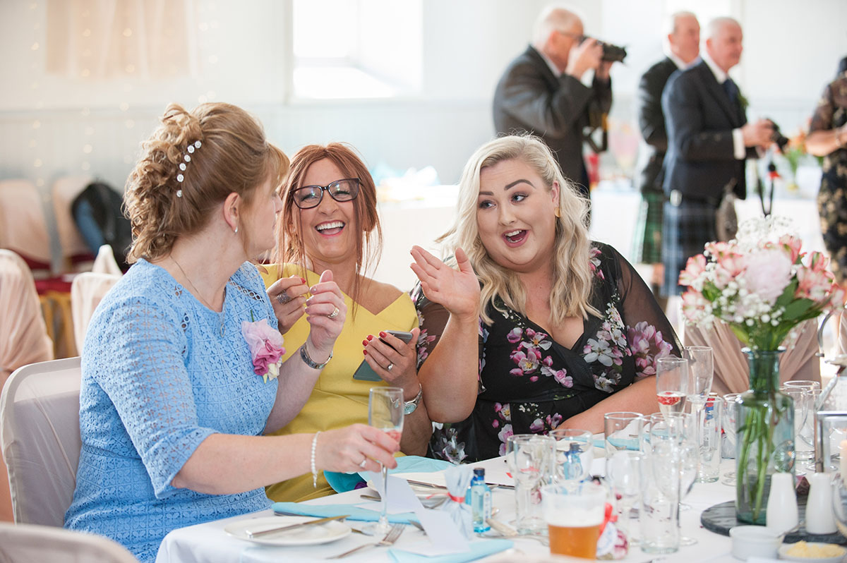 Wedding photos - three female wedding guests seated at a table laughing and gesticulating with their hands