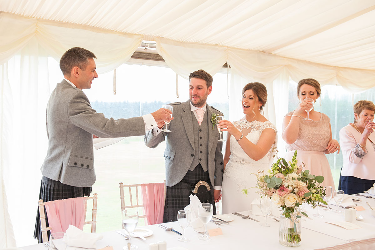 Wedding photos - best man and bride and groom standing and raising their glasses in a toast at a wedding