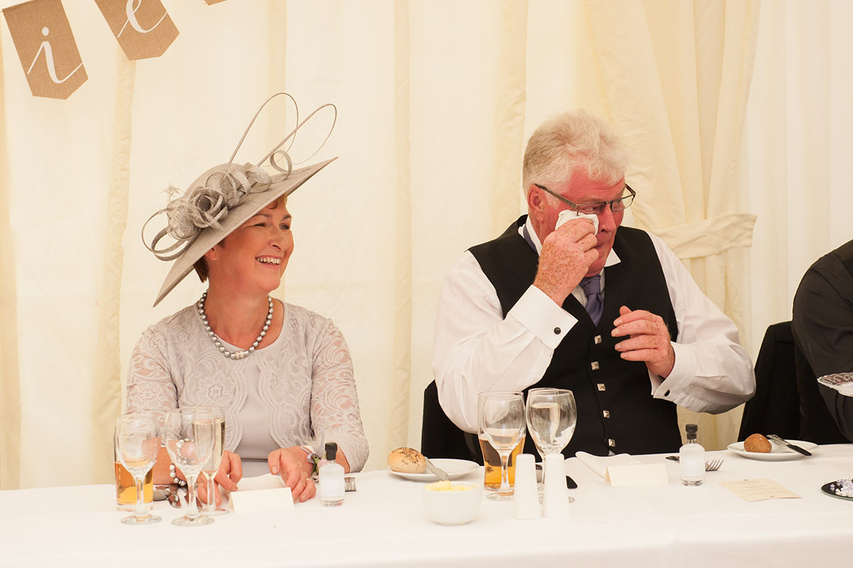 Wedding photos - woman with a cream hat sitting beside a man in a waistcoat wiping his eyes with a handkerchief