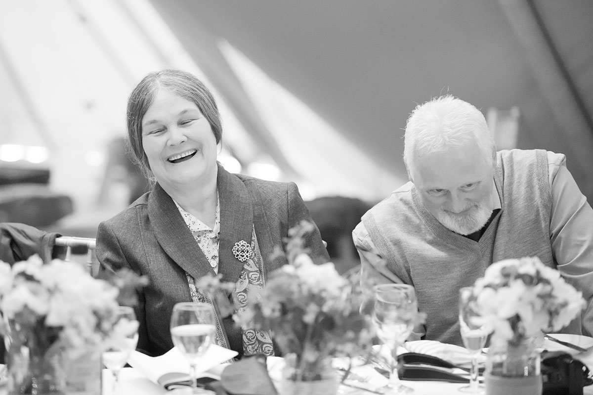 Wedding photos - monochrome image of a man and woman laughing while seated at a table with flowers, during wedding speeches