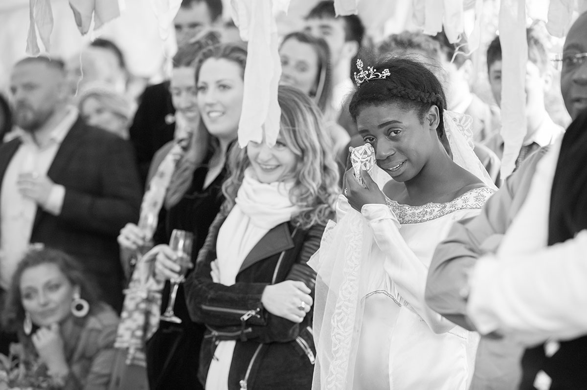 Wedding pictures - monochrome image of a bride dabbing her eyes with her veil, surrounded by wedding guests