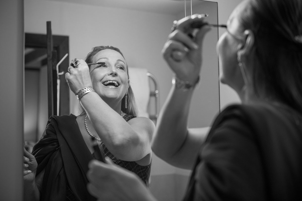 Wedding pictures - monochrome image of a bride in a dark dress smiling and applying mascara to her eyelashes in a mirror