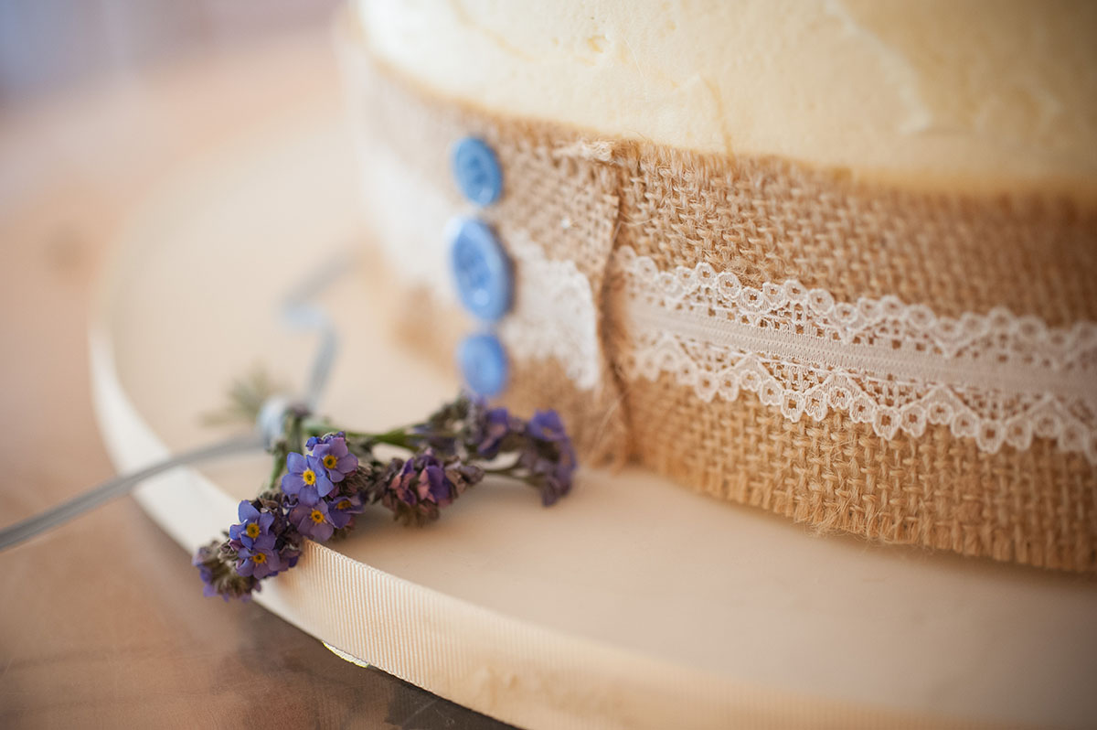Wedding pictures - forget-me-nots placed next to a cream wedding cake with three blue buttons on the cake ribbon