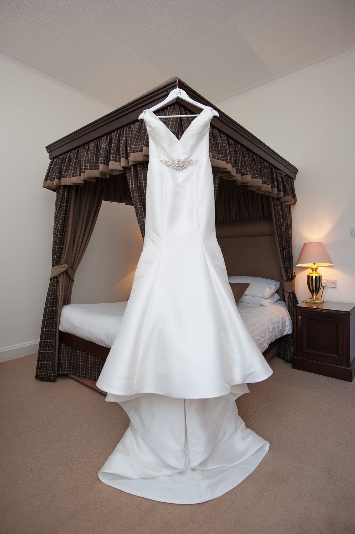 Wedding portfolio - white silk wedding dress hanging on the end of a brown four poster bed in a room with a pale pink carpet