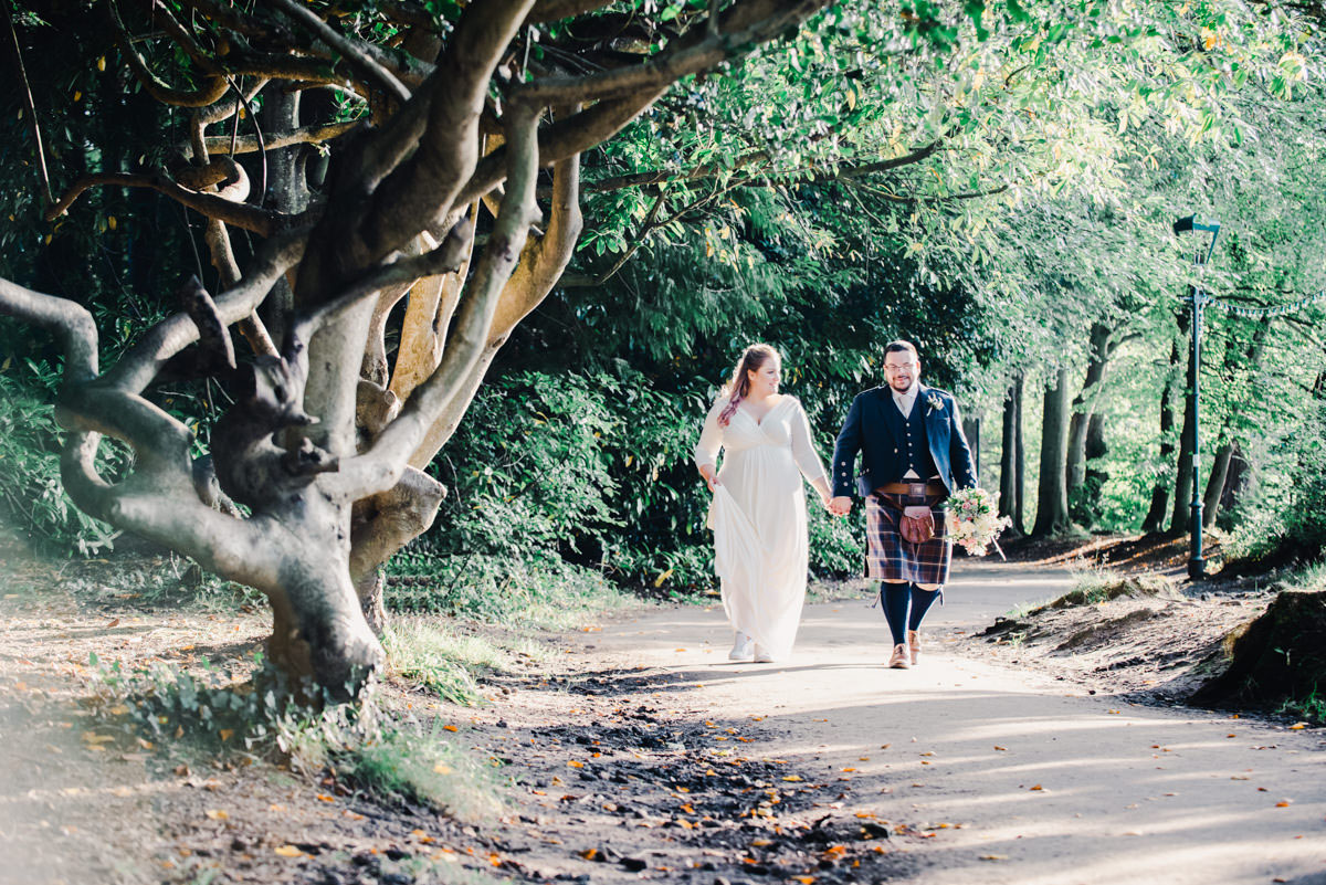 A bride and groom holding hands and walking on a path in a woodland, with a twisted tree trunk on one side