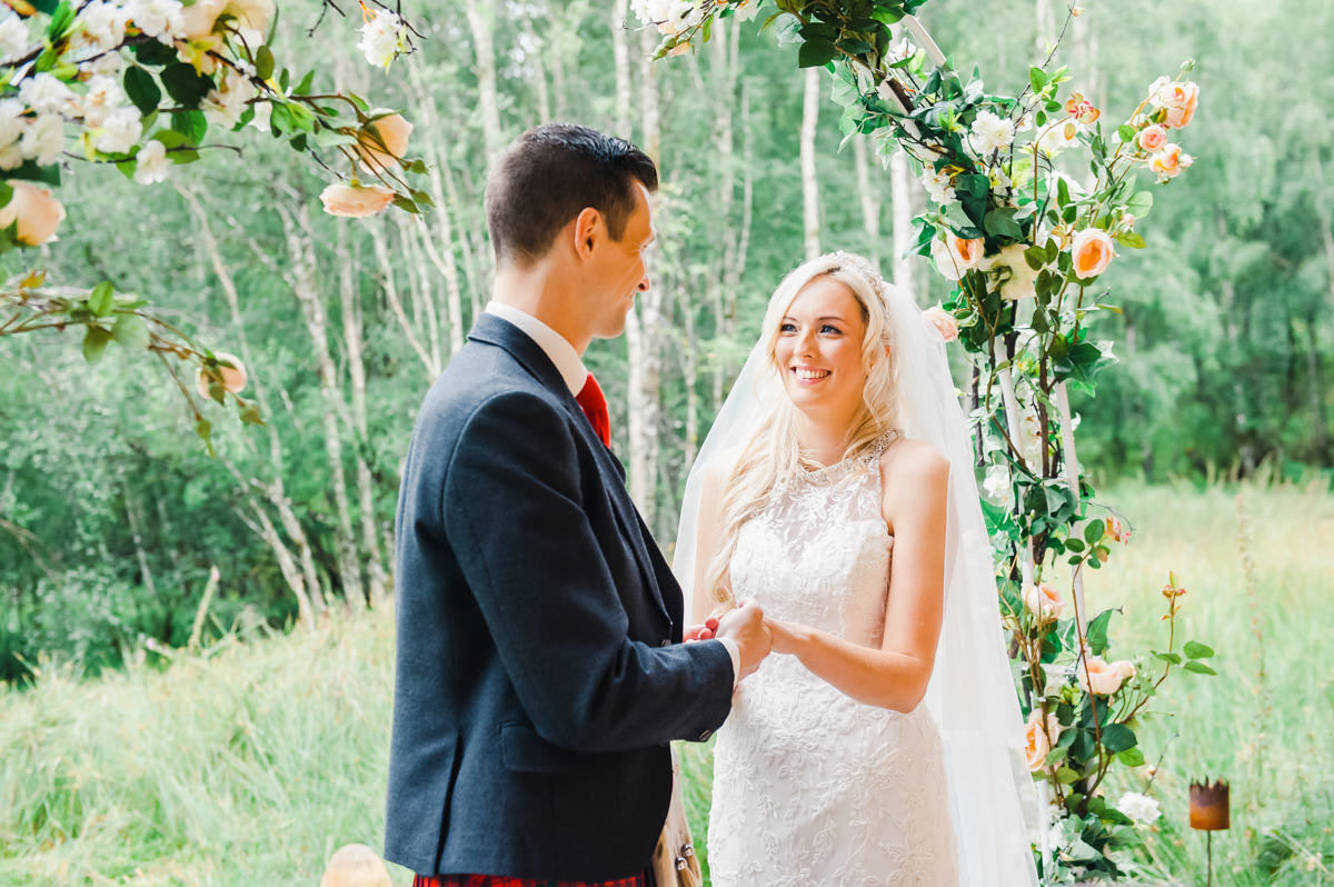An outdoor wedding ceremony with the bride smiling at the groom under an archway of flowers with green trees and grass beyond