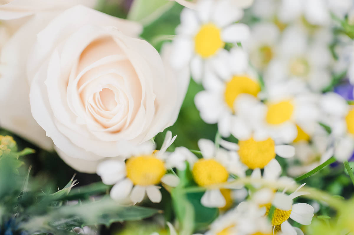 Wedding photograph of a pale pink rose and yellow and white daisies in a bride's bouquet of flowers