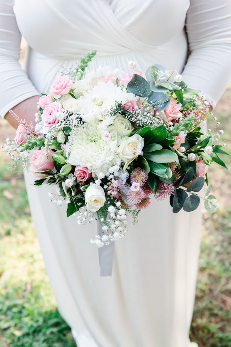 A close-up wedding photograph of a bride holding a bouquet of cream, pink and green flowers