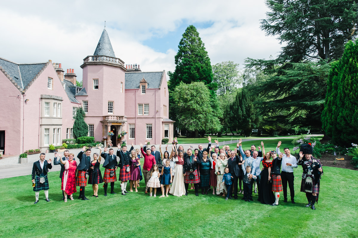 A wedding photo of a bride and groom and their guests waving while standing on a lawn in front of a pink castle and trees