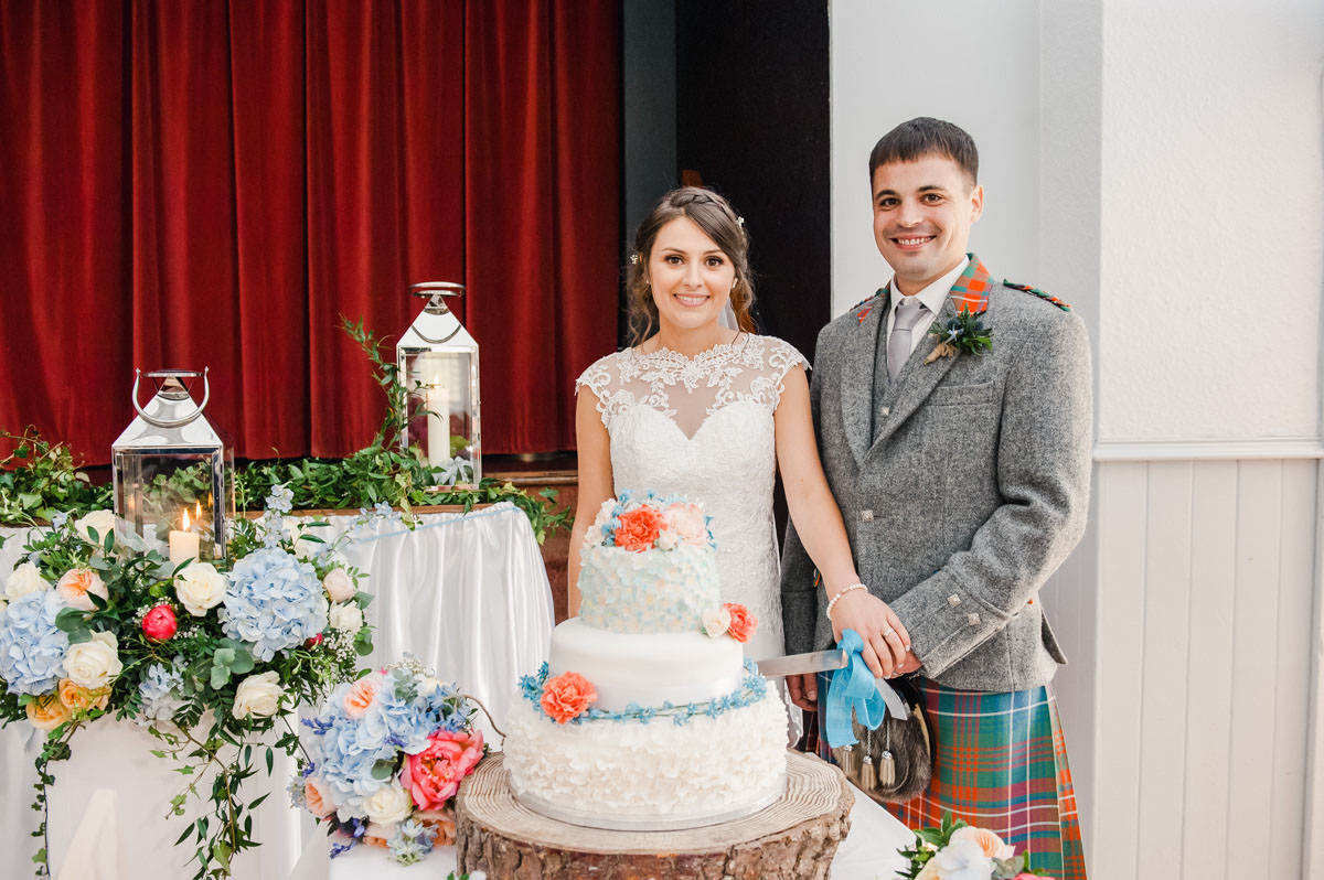 A wedding photo of a bride and groom ready to cut their wedding cake, with flowers and candles to one side