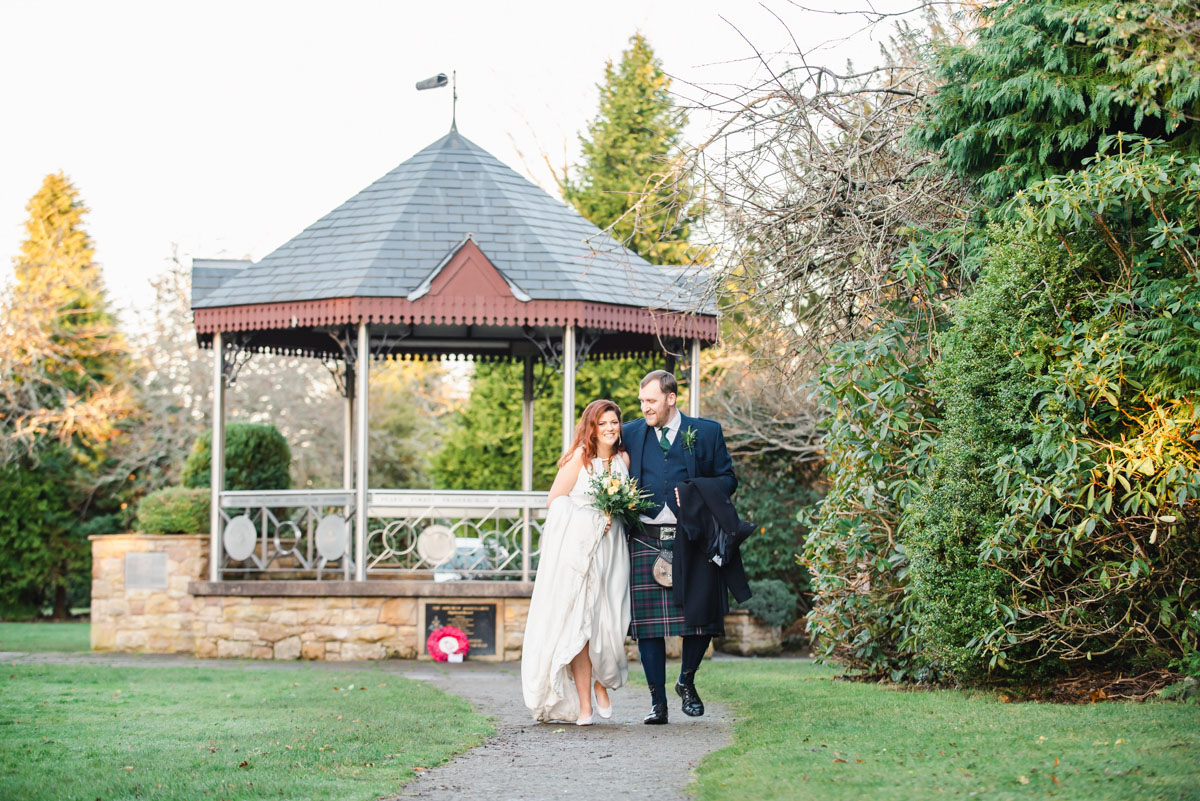 A bride and groom smiling and walking on a path through a park with a bandstand and trees in the background