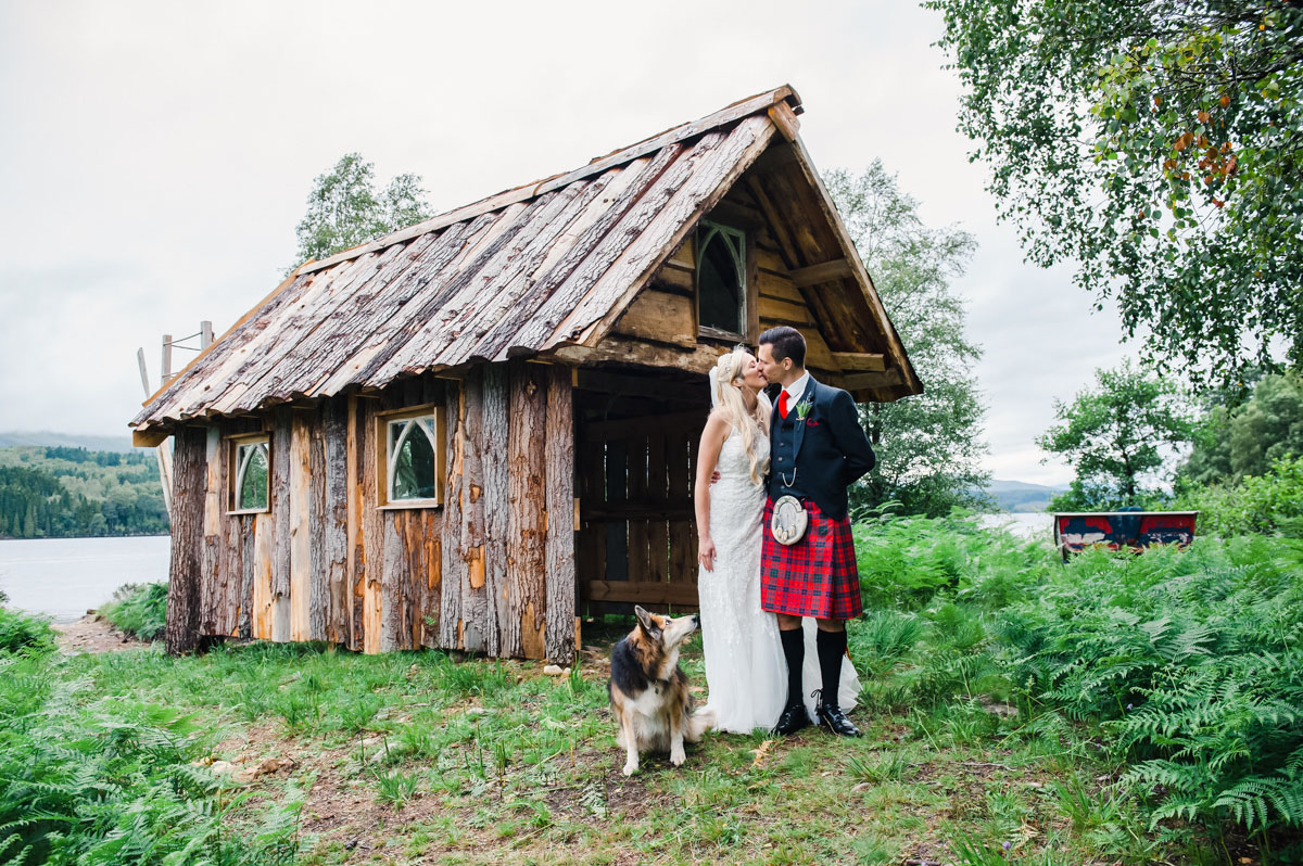 A bride and groom standing and kissing in front of a wooden boat shed and green ferns, with their dog looking up at them