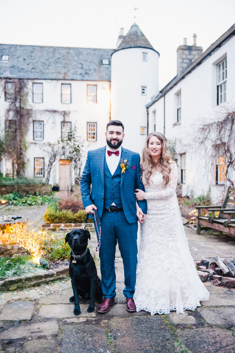 Wedding photograph of a bride and groom with a black dog standing in a courtyard in front of a white building with a turret