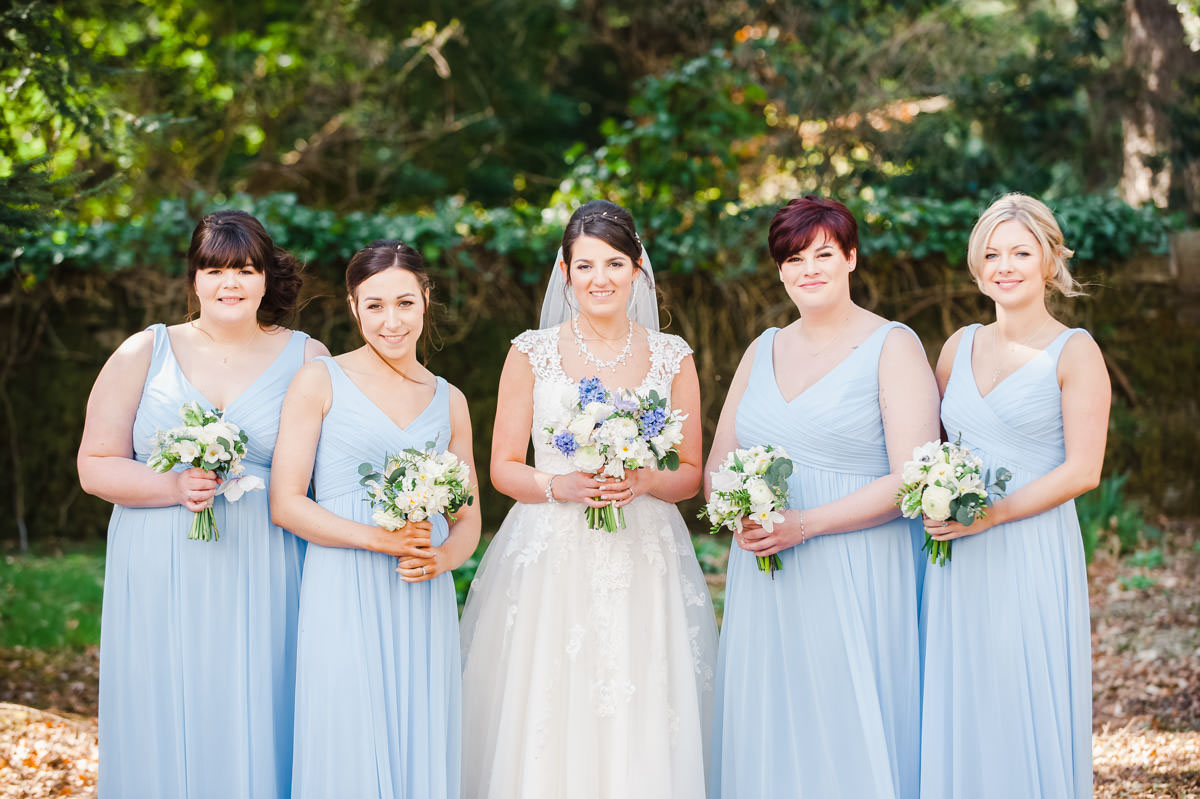 Wedding photograph of a bride with four bridesmaids in blue dresses, all holding flowers, standing in front of trees