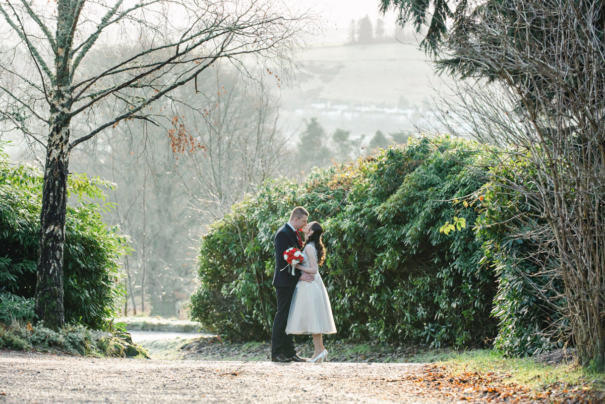 A wedding photo of a bride and groom kissing in front of a green hedge and trees, with houses on a hill in the distance