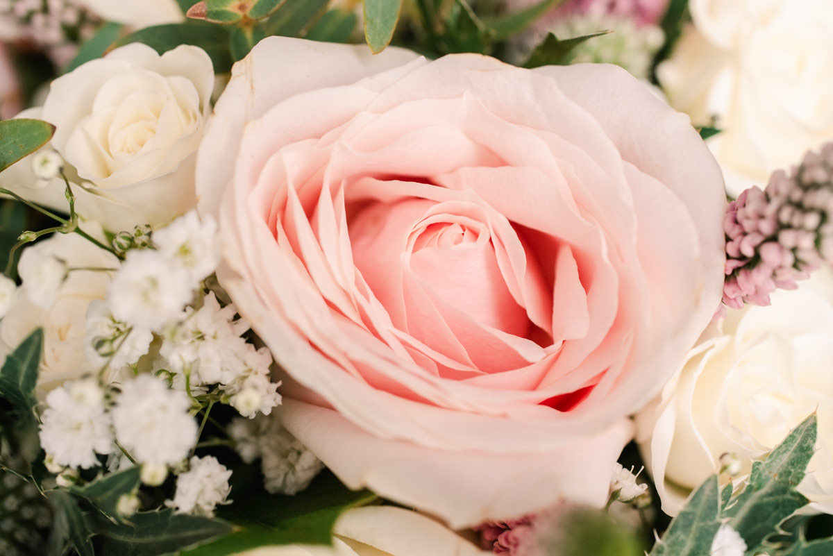 A close-up photograph of a beautiful pink rose in a bouquet of wedding flowers