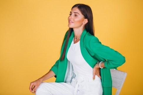 mujer-chaqueta-verde-sentado-silla-sobre-fondo-amarillo_1303-10384