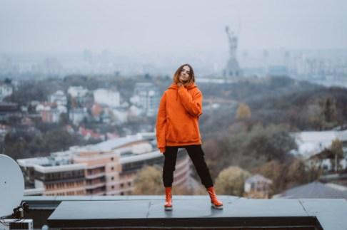 mujer-joven-chaqueta-naranja-posa-techo-edificio-centro-ciudad_1153-5135