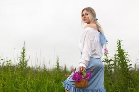 mujer-joven-falda-azul-blusa-blanca-camina-sobre-campo-canasta-flores_153274-212