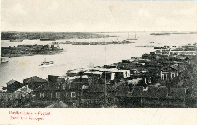 1900-luvun alussa kuvattu postikortti Kaupunginlahden suulta. Kortin tekijä on ymmärtänyt lahden joeksi, mikä näkyy myös otsikossa. Vanhan kirkon tornista kohti länttä otetussa kuvassa näkyy etualalla kaupungin viimeisiltä tulipaloilta säästyneitä, jo 1700-luvulla rakennettuja Baltzaborgin taloja, uutta möljää, rantamakasiineja ja lautatapuleita. Kohti kaupungin keskustaa matkaa saaristohöyrylaiva, joilla matkattiin lähiseudun kohteiden lisäksi aina Helsinkiin, Turkuun, Raumalle ja Poriin asti. Ensimmäinen uusikaupunkilaisten rakennuttama höyrylaiva oli Ebba Munck, jolla oli tarkoitus ajaa Tukholmaan asti myös talvella. Laivoilla kuljetettiin ennen rautatien tuloa myös postia. Kuvan oikeassa laidassa mäen päällä nykyisin luotsimuseona toimiva vanha luotsiasema.