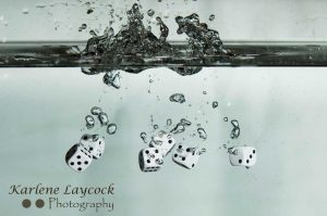 White Dice falling into water on grey 2