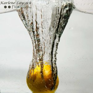 Lemon falling into water on grey 2
