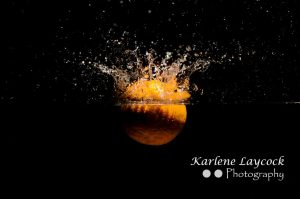 Orange dropping into water on black background 1