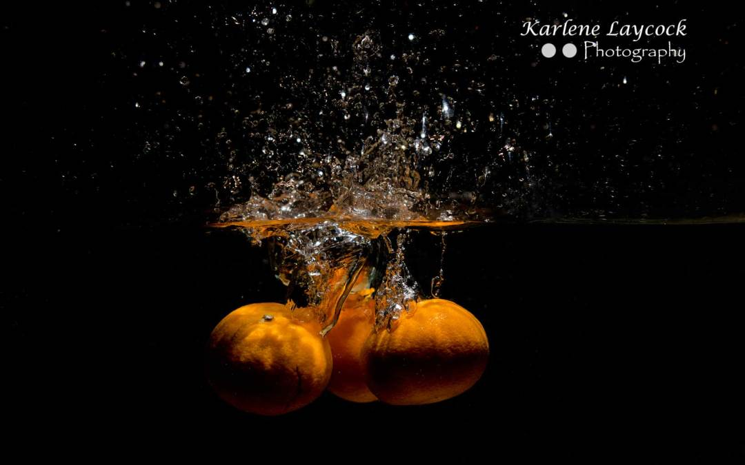 3 Orange dropping into water on black background 3