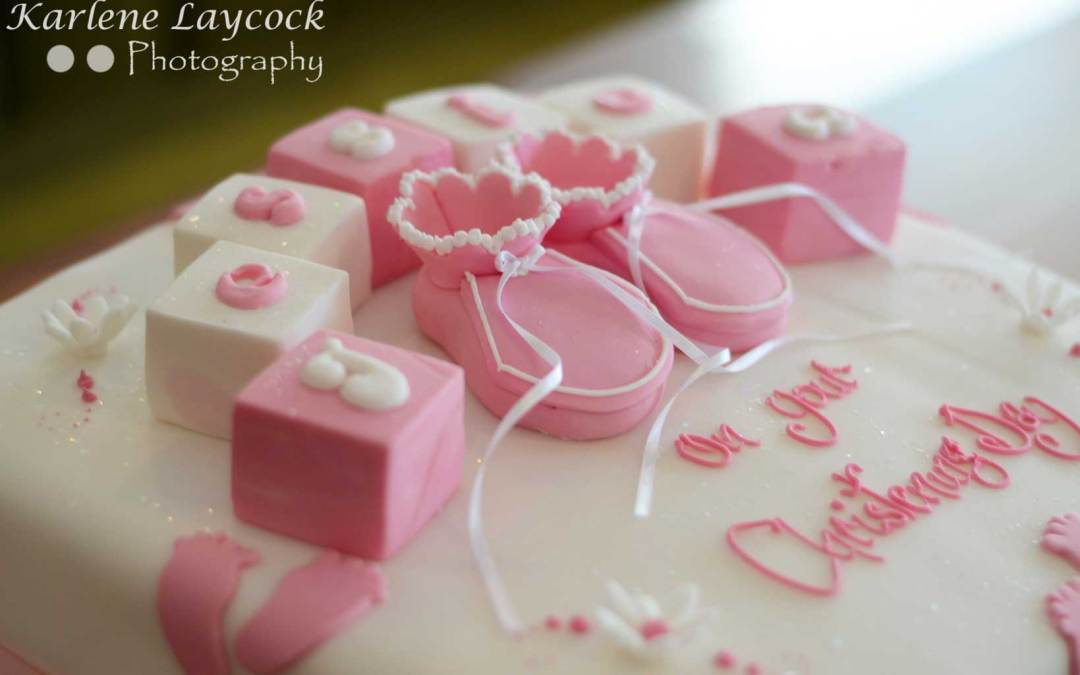Photograph of a Pink Christening Cake with Booties and Building Blocks