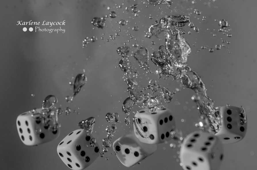 High Speed Photography – Six White Dice Floating against a Grey Background