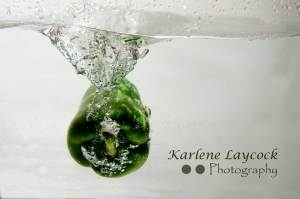 Green Pepper Submerged against a Grey Background with a Vortex Wave