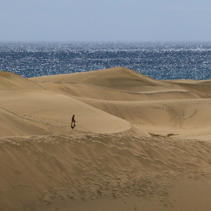 A lone visitor wanders through the sand dunes of Maspalomas. The sea is blue and glittering in the background.