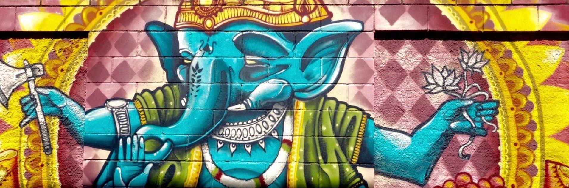 Auf diesem Bild ist ein buntes Graffiti an einer Hauswand zu sehen. Es zeigt sehr farbenfroh die hinduistische Gottheit Ganesha. Ganesha ist der Gott mit den vielen Armen und dem Elefantenkopf. Er steht unter anderem für die Kraft, HIndernisse aus dem Weg zu räumen.