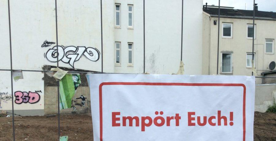 """Hier ist ein Bild von einem Bauzaun zu sehen. Auf einem Din A 4 Zettel, der am Bauzaun hängt, steht: """"Empört Euch!"""""""