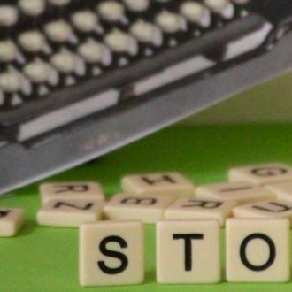 """Auf diesem Bild sind aufgestellte Buchstaben zu sehen, die den Schriftzug """"Story"""" bilden. Im Hintergrund ist eine Schreibmaschine."""